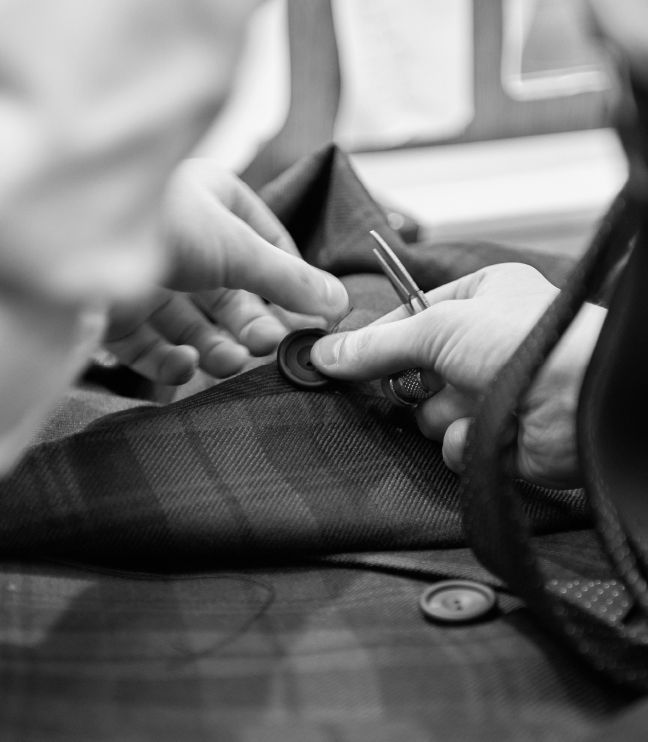 Huntsman Bespoke Experience Gallery Image - Tailor sewing jacket button